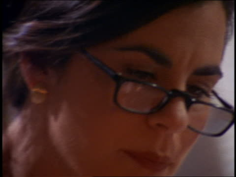 close up woman wearing reading glasses working on computer