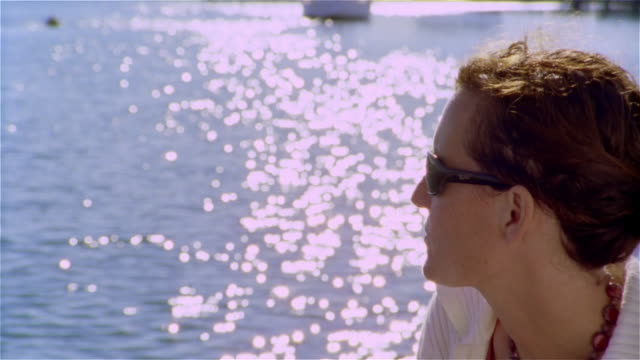 close up woman wearing sunglasses looking out at sun-dappled water - only mid adult women stock videos & royalty-free footage
