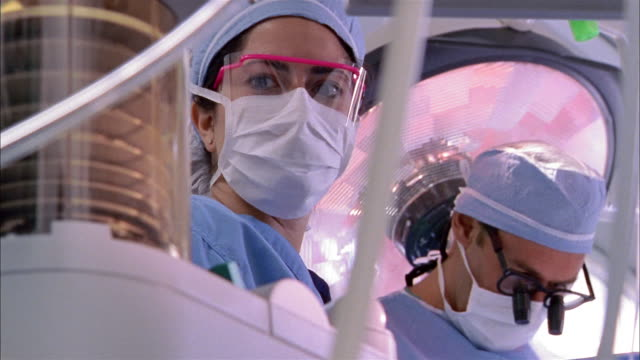 close up woman wearing surgical mask adjusting and monitoring respirator in operating room - respiratory machine stock videos & royalty-free footage