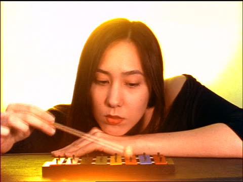 close up woman with head resting on hand playing xylophone in studio - londonalight点の映像素材/bロール