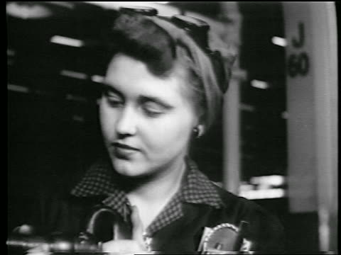 B/W 1944 close up woman with kerchief on head riveting in defense plant / World War II / industrial