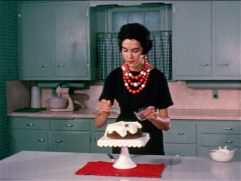 vídeos de stock e filmes b-roll de 1950 close up woman with large necklace spooning grated chocolate onto icing covered cake / industrial - 1950