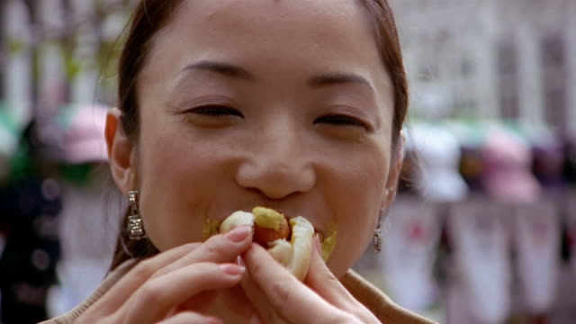 Close up woman with mustard on her face stuffing hot dog into her mouth and looking at CAM / New York City