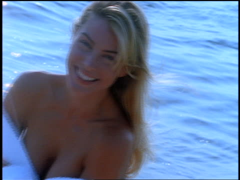 canted rear view close up woman with robe stands in front of water / she turns and smiles + laughs at camera - 1998 stock videos & royalty-free footage