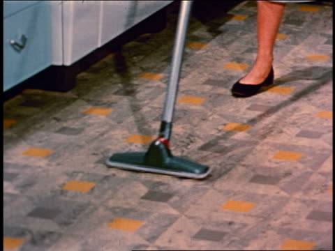 1950 close up woman with vacuum cleaner hose + attachment vacuuming kitchen floor