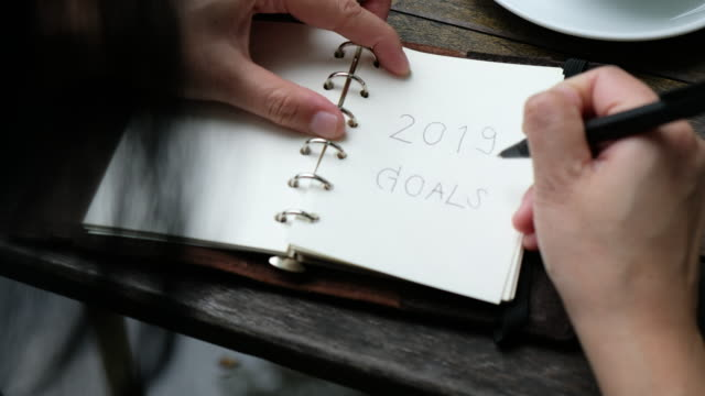 vídeos de stock e filmes b-roll de close up woman writing 2019 goals on notebook plan for new year and drink coffee on wood table - fim
