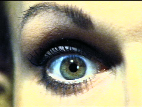 vidéos et rushes de overexposed close up woman's eye with makeup narrowing, widening + blinking / flash frame - overexposed