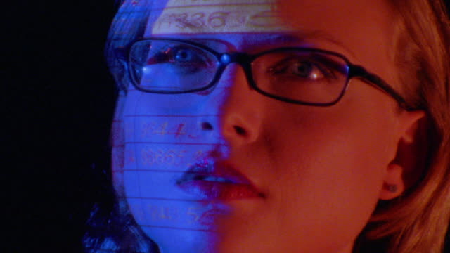 close up woman's face with eyeglasses reflecting spreadsheet on computer screen / she turns to side - quotazione di borsa video stock e b–roll