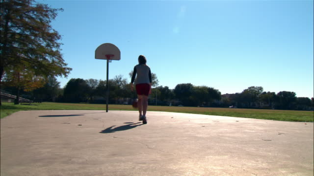 close up woman's feet and basketball as she picks it up off ground/ wide shot woman running and shooting baskets/ dallas, texas - nike designer label stock videos and b-roll footage