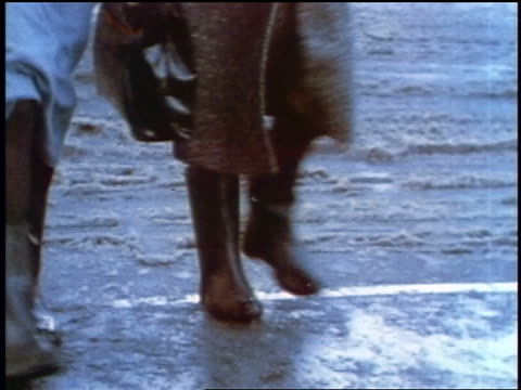 1957 close up woman's feet in high heels standing on wet street / women's feet in boots walking in slush