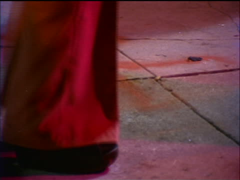 1974 close up woman's feet in platform shoes + bell bottoms dancing / PAN to man's feet dancing