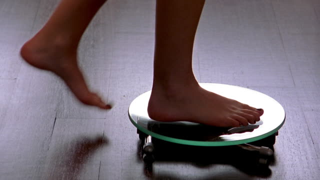 close up woman's feet stepping onto scale on wood floor and stepping off  + walking away - waage gewichtsmessinstrument stock-videos und b-roll-filmmaterial