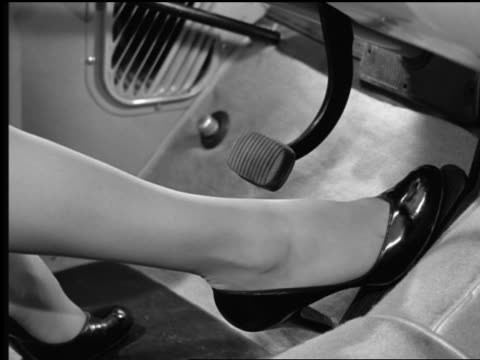B/W 1954 close up woman's foot moving from gas pedal to brake in car