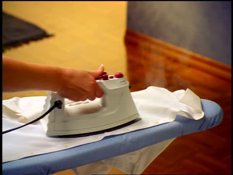 vidéos et rushes de close up woman's hand ironing shirt on ironing board - fer