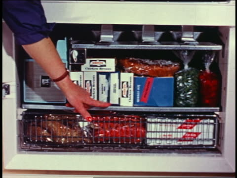1958 close up woman's hand pointing to shelves of food-filled freezer - cibi surgelati video stock e b–roll