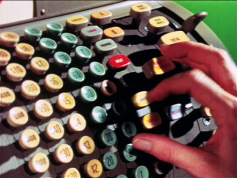 1965 close up woman's hand pushing buttons on cash register / educational