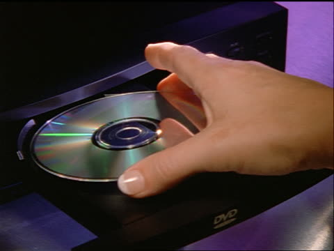 stockvideo's en b-roll-footage met close up woman's hand putting dvd into dvd player + closing - dvd