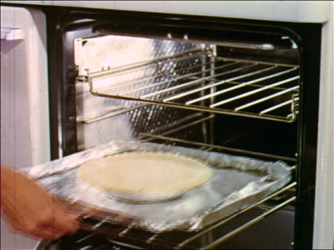 1955 close up woman's hand putting pie in oven / industrial