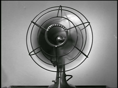 B/W 1955 close up woman's hand switching on desktop rotating fan / industrial