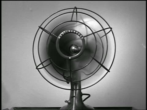 vidéos et rushes de b/w 1955 close up woman's hand switching on desktop rotating fan / industrial - rafraîchissement