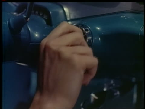 1957 close up woman's hand turns key in ignition of Chevrolet Impala