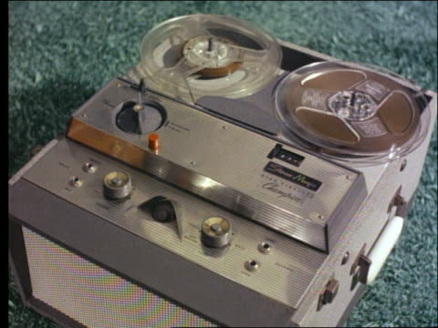 close up woman's hand turns knob on reel to reel tape recorder / 1950's