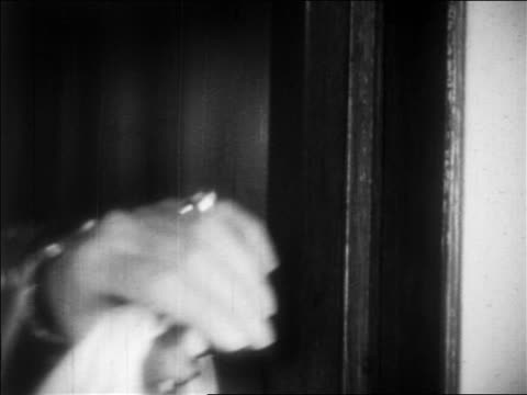 B/W 1932 close up woman's hand with bracelets reaching to open door / feature
