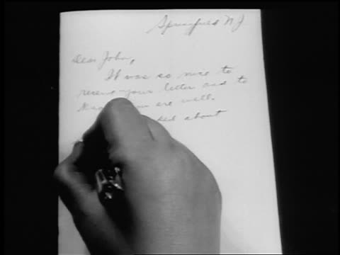 vídeos de stock, filmes e b-roll de b/w 1943/44 close up woman's hand writing letter with pen / newsreel - escritor