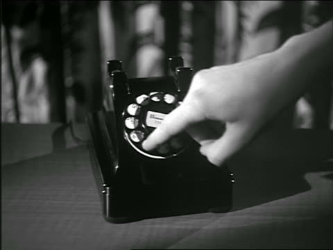 b/w 1950 close up woman's hands dialing on black rotary phone - disco combinatore video stock e b–roll