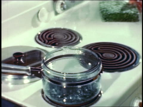 1946 close up woman's hands emptying packet of frozen peas into saucepan of boiling water on stove - boiling water stock videos and b-roll footage