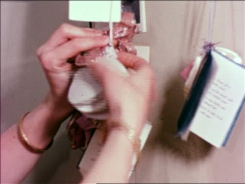 vídeos de stock e filmes b-roll de 1951 close up woman's hands hanging cards on string / educational - 1951
