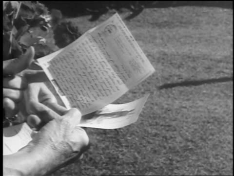 vídeos de stock, filmes e b-roll de b/w 1943/44 close up woman's hands holding letter + flowers / springfield, nj / newsreel - 1943