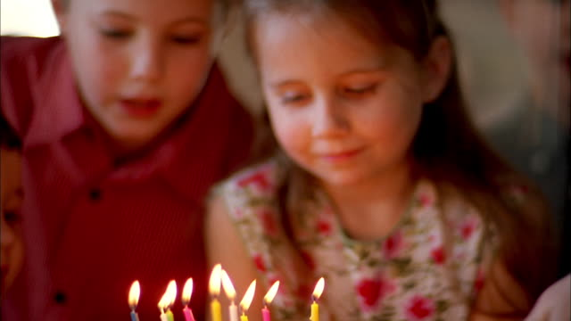 close up woman's hands placing birthday cake w/candles in front of young girl /  blowing candles - birthday cake stock videos & royalty-free footage
