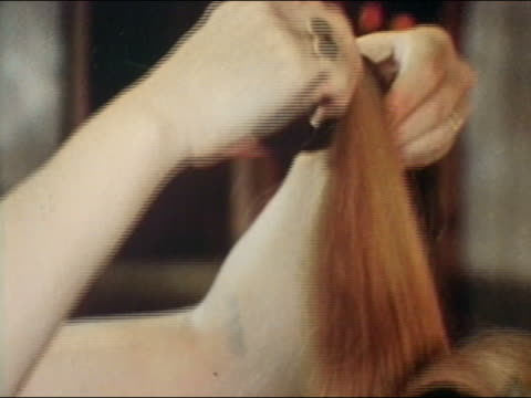 1969 close up woman's hands placing rollers in woman's hair / AUDIO