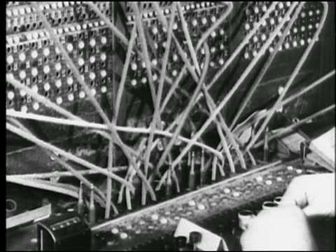 b/w 1925 close up woman's hands plugging in cables on telephone switchboard / newsreel - 電話交換機点の映像素材/bロール