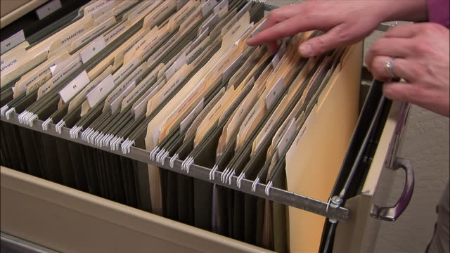 close up woman's hands pulling file from file cabinet/ arizona - file stock videos & royalty-free footage