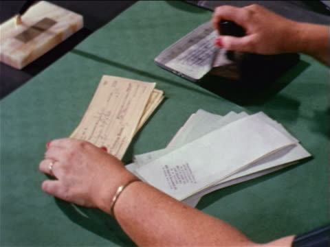 1962 close up woman's hands rubber stamping backs of checks / educational - cheque financial item stock videos & royalty-free footage