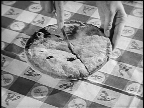 B/W 1950 close up woman's hands slicing pie with knife on table