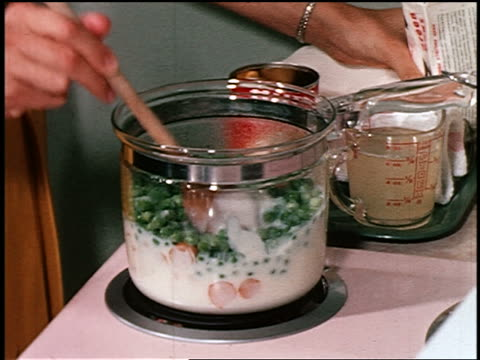 1950 close up woman's hands stirring frozen peas + canned potatoes into pot with cream on stove - cibi surgelati video stock e b–roll
