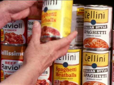 vidéos et rushes de 1964 close up woman's hands taking canned spaghetti + meatballs from shelf + turning it to read label - société de consommation
