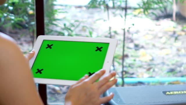 vídeos y material grabado en eventos de stock de primer plano de mujer sosteniendo en blanco de tablet pc con pantalla verde - detrás