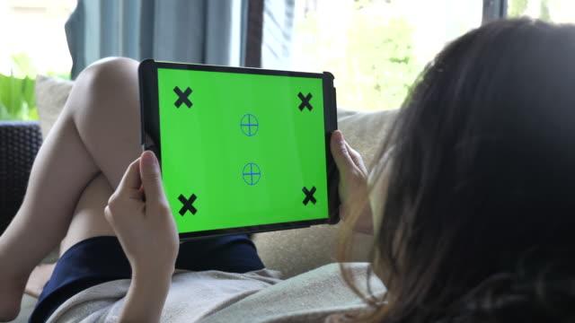 närbild kvinnor håller tom tablet pc med grön - över axel perspektiv bildbanksvideor och videomaterial från bakom kulisserna