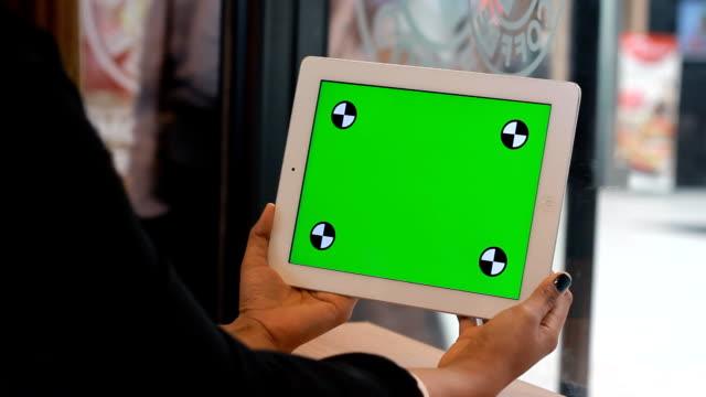 vídeos y material grabado en eventos de stock de primer plano de mujer sosteniendo en blanco de tablet pc con verde - detrás