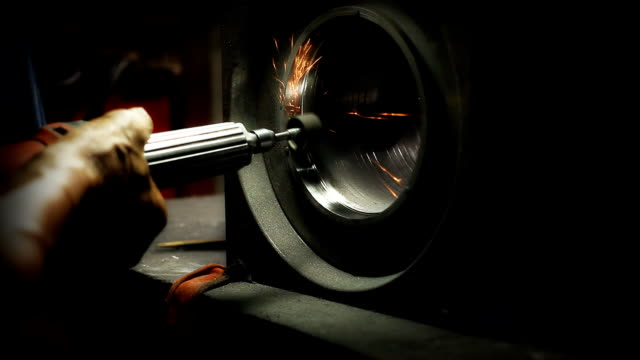 close up workers operate an industrial grinder on a piece of steel. - bugtiger stock videos and b-roll footage