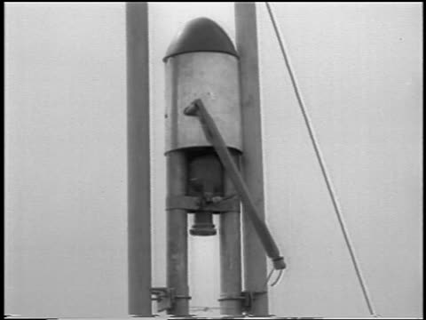 B/W 1933 close up world's first liquidfueled rocket preparing to launch / newsreel