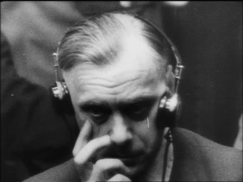 b/w 1945/46 close up worried alfred rosenberg with headphones at war crime trials / nuremberg / documentary - 中年の男性一人点の映像素材/bロール