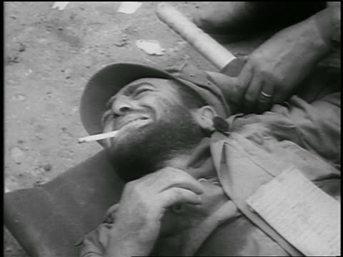 b/w 1950 close up wounded soldier smoking cigarette lying on stretcher in pain / korean war / newsreel - solo uomini di età media video stock e b–roll