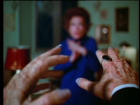 close up wrinkly hands reaching toward out-of-focus woman in background - horror movie stock-videos und b-roll-filmmaterial
