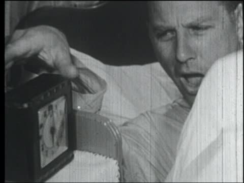 b/w 1958 close up yawning man in bed turning off alarm clock - alarm clock stock videos & royalty-free footage