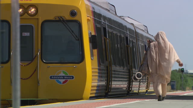 close up yellow adelaide metro train pulls up to platform anon woman seen from rear wearing full head covering and matching clothes and carrying... - matching outfits stock videos & royalty-free footage
